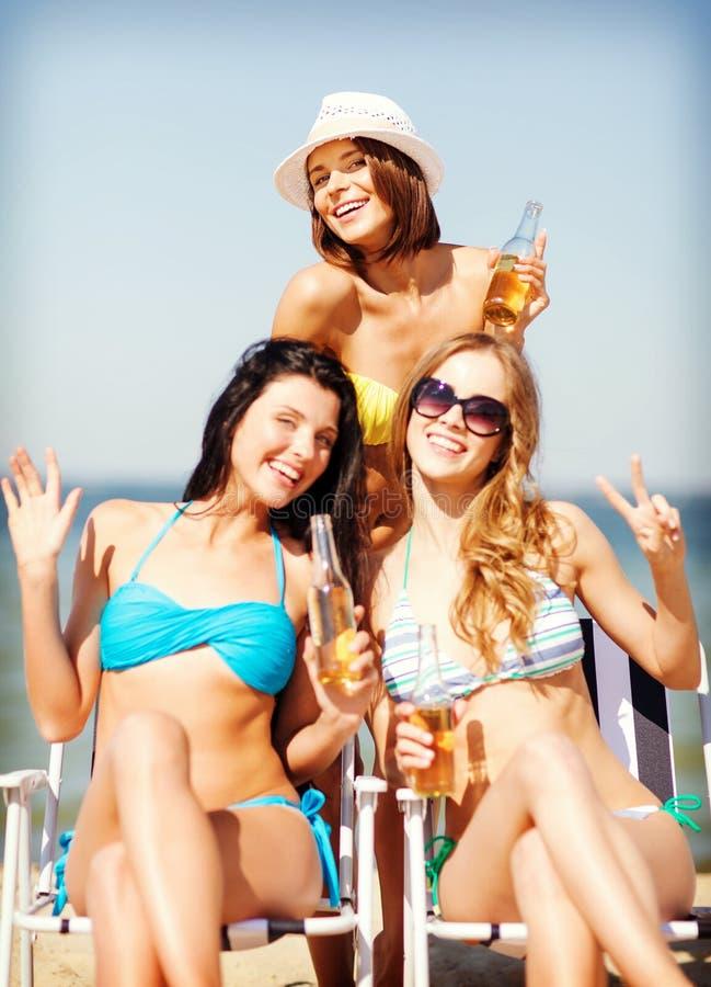 Meninas com bebidas nas cadeiras de praia fotos de stock