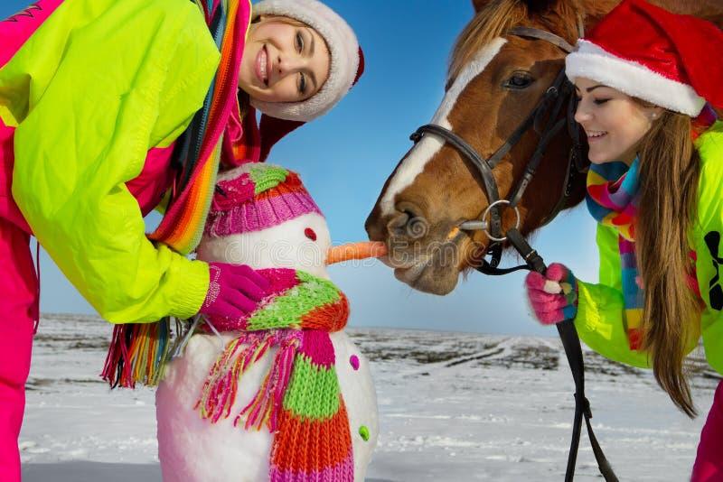Meninas com cavalo e boneco de neve foto de stock royalty free