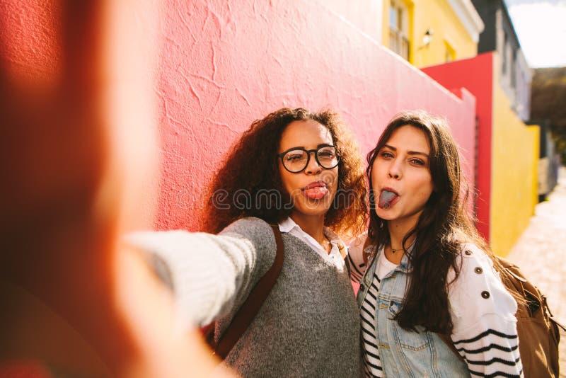 Meninas com a língua colorida que toma o selfie foto de stock