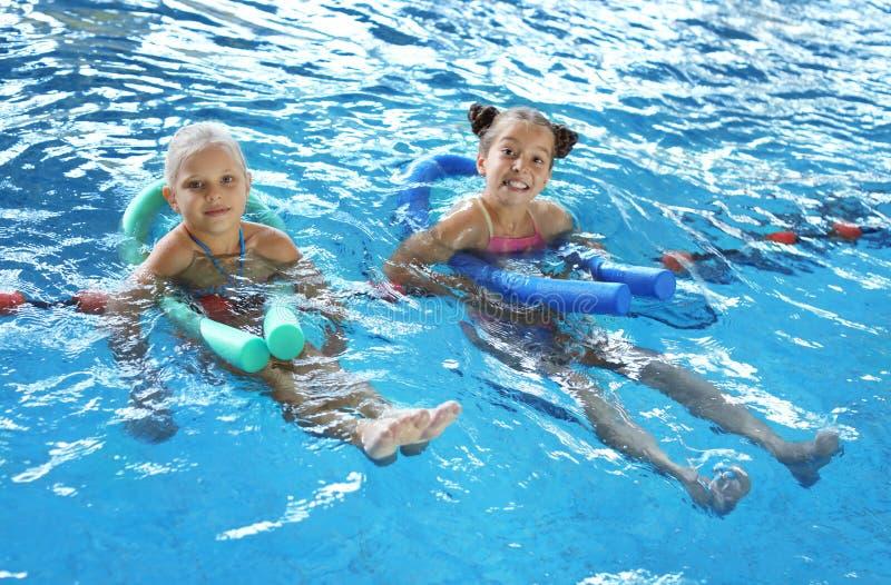 Meninas com macarronetes da natação imagens de stock royalty free