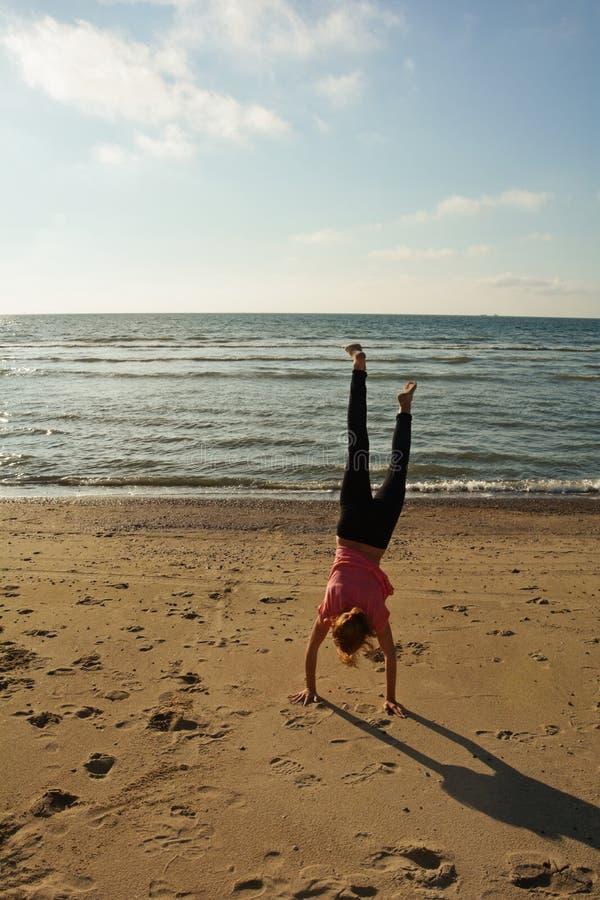 Meninas com o estado da mão no Sandy Beach na costa de Mar do Norte imagens de stock
