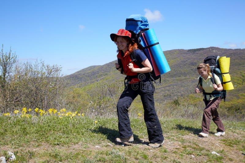 Meninas com o passeio dos backpaks ao ar livre foto de stock