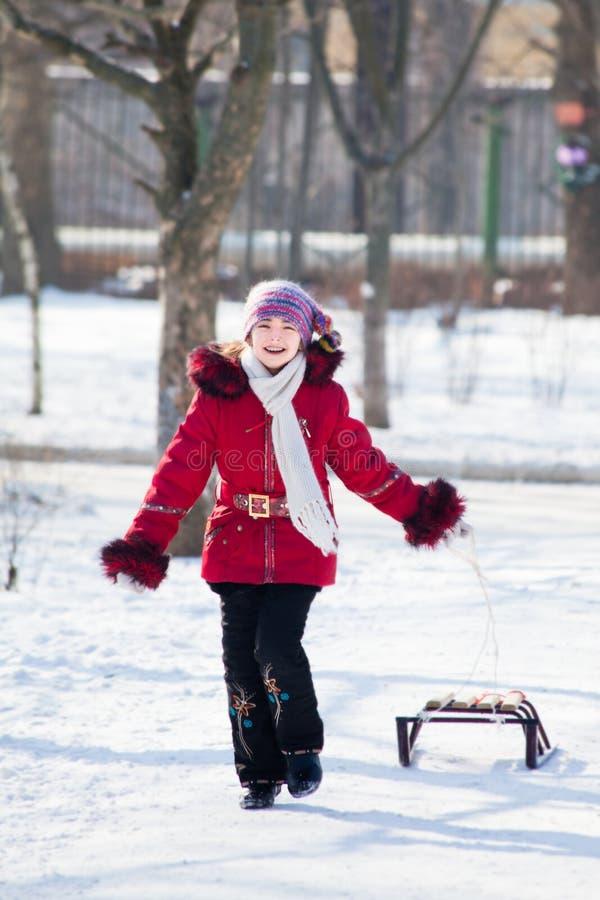 Meninas com resto do pequeno trenó na neve do inverno foto de stock royalty free