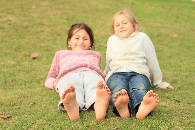 Meninas com smiley nos dedos do pé imagens de stock