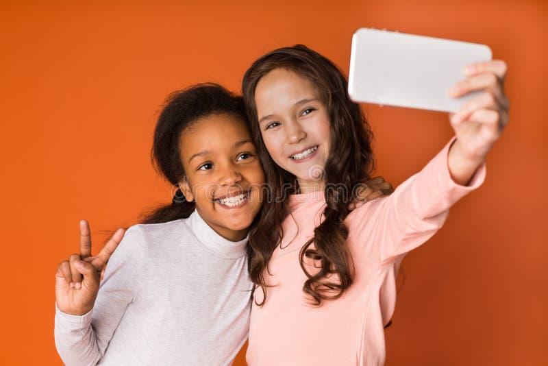 Meninas da criança que fazem o selfie no smartphone sobre o fundo alaranjado imagem de stock
