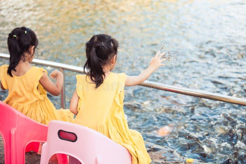 Meninas da criança que têm o divertimento para alimentar e dar o alimento aos peixes imagens de stock royalty free