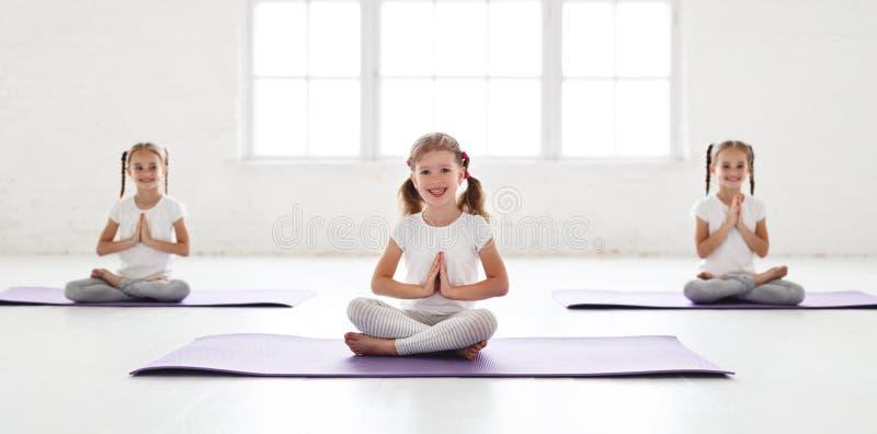 Meninas das crianças que fazem a ioga e a ginástica no gym fotografia de stock royalty free