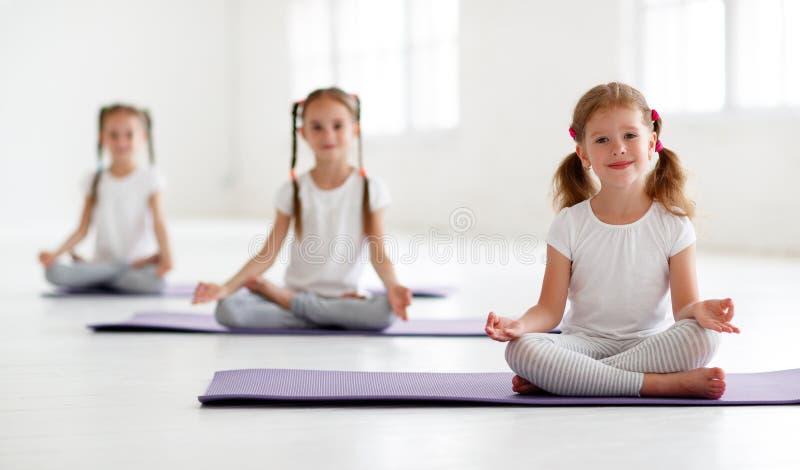 Meninas das crianças que fazem a ioga e a ginástica no gym fotografia de stock