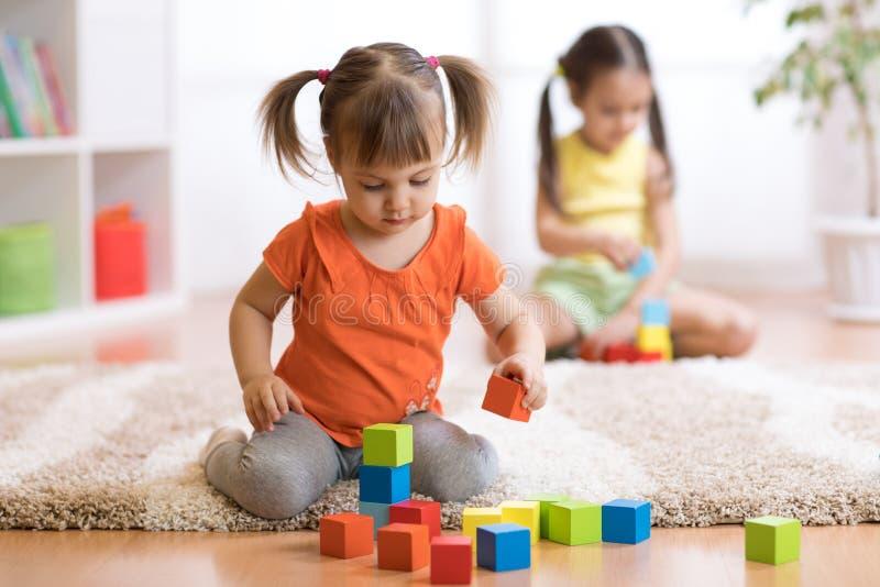 Meninas das crianças das crianças que jogam brinquedos em casa, jardim de infância ou berçário fotografia de stock