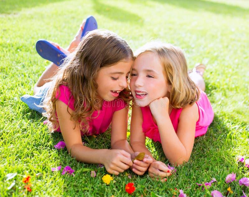 Meninas das crianças que jogam o sussurro na grama das flores fotografia de stock royalty free
