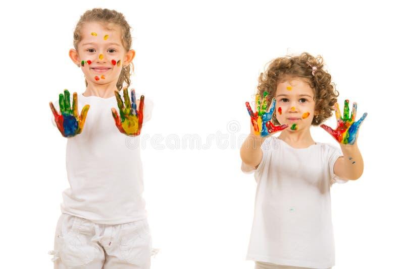 Meninas das irmãs mais nova que mostram as mãos pintadas fotografia de stock royalty free
