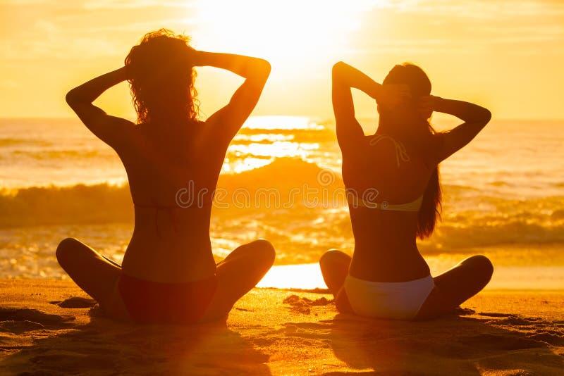 Meninas das mulheres que sentam a praia do biquini do por do sol do nascer do sol fotografia de stock