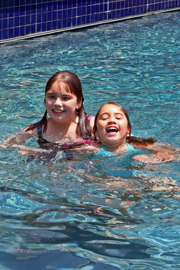 Meninas de sorriso na piscina imagens de stock royalty free