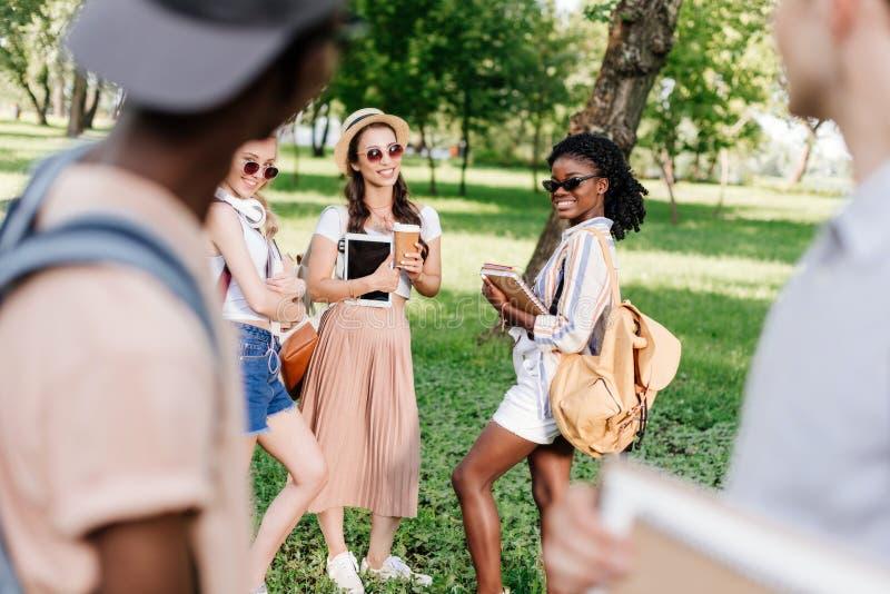 Meninas de sorriso nos óculos de sol que guardam livros e a tabuleta digital ao olhar meninos no primeiro plano fotos de stock royalty free