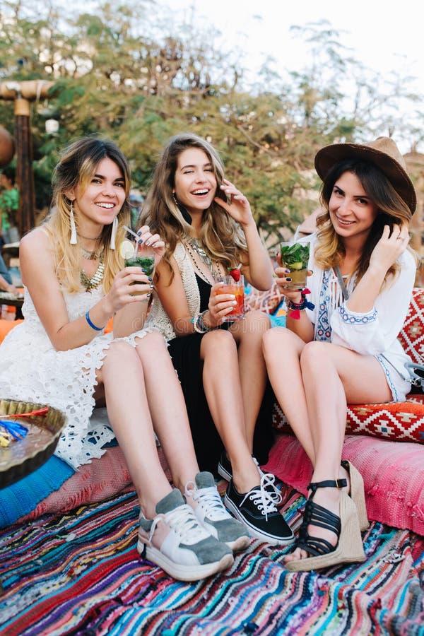 Meninas de sorriso novas atrativas em vestidos na moda que passam o tempo junto no piquenique do verão no parque Retrato de alegr imagens de stock
