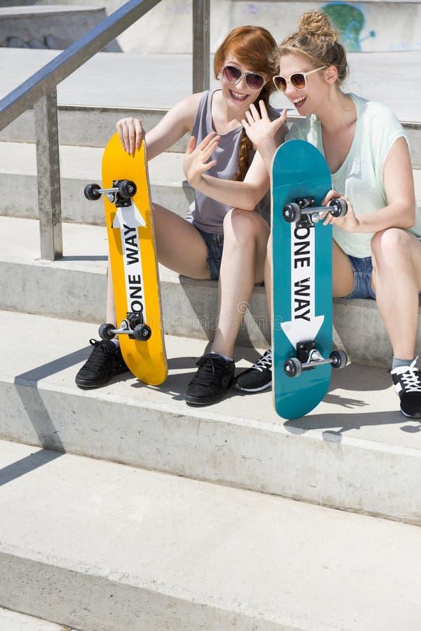 Meninas de sorriso que sentam-se com skates imagens de stock royalty free