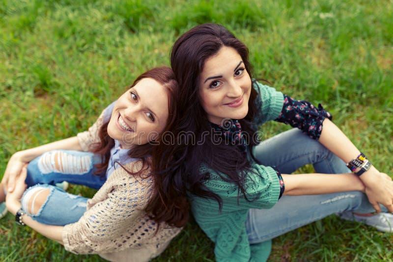 Meninas de sorriso que sentam-se de volta à parte traseira na grama fotos de stock royalty free