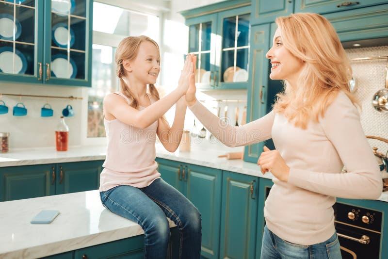 Meninas deleitadas positivas que tocam nas mãos com prazer fotografia de stock royalty free
