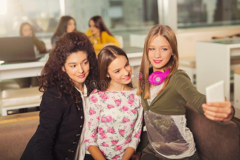 Meninas do adolescente que penduram para fora junto em uma cafetaria imagens de stock royalty free