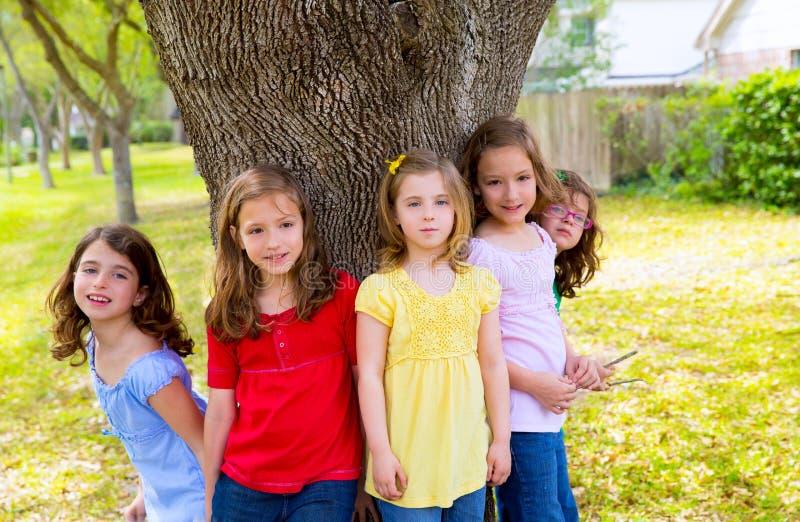 Meninas do amigo do grupo das crianças que jogam na árvore fotografia de stock royalty free