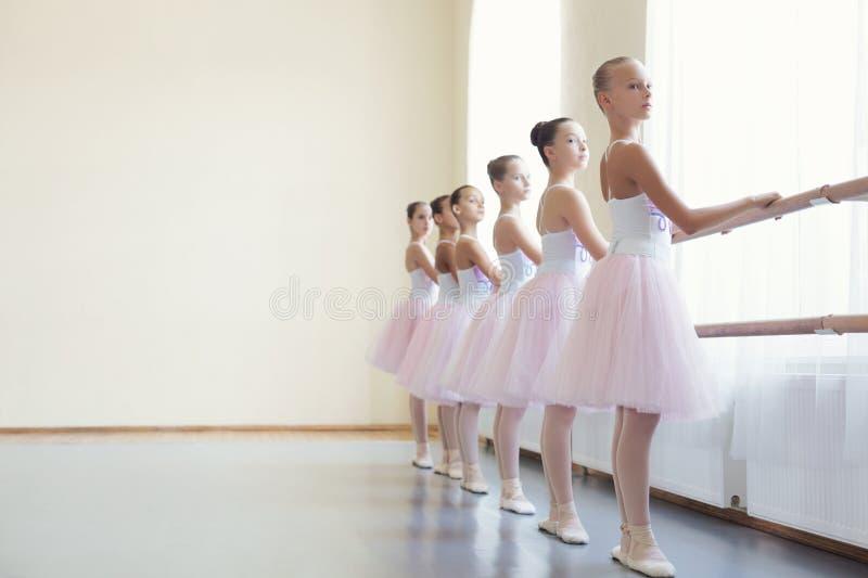 Meninas do bailado que treinam antes do desempenho na classe de dança imagem de stock