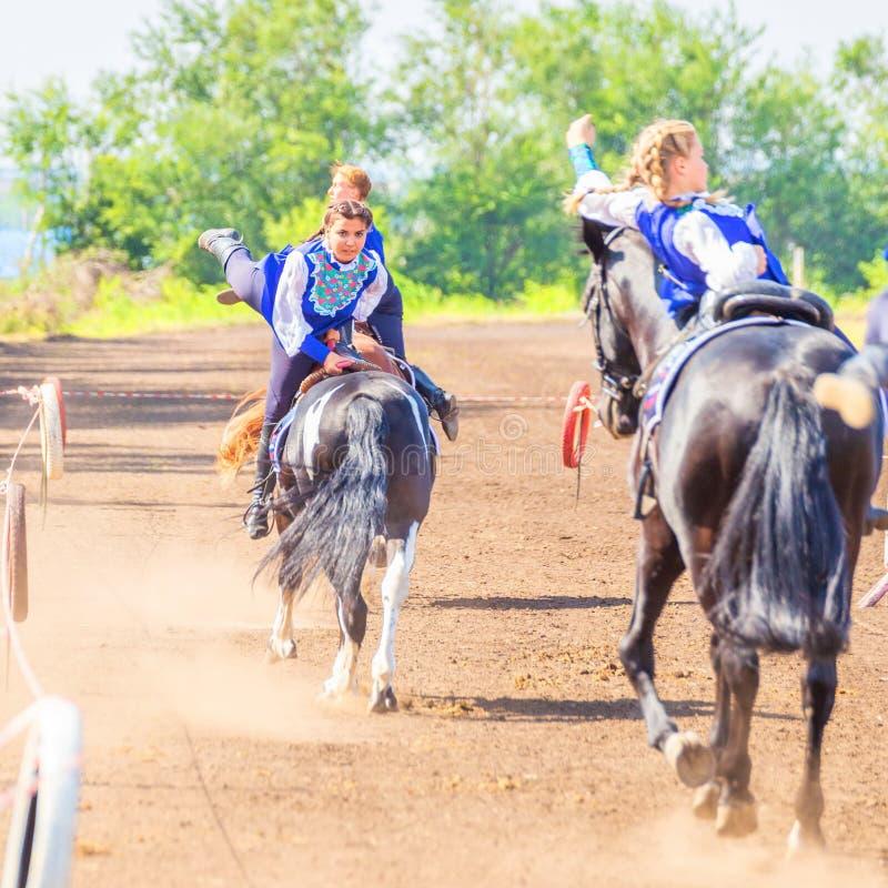 Meninas do grupo de dzhigitovki para executar a cavalo truques complexos imagem de stock