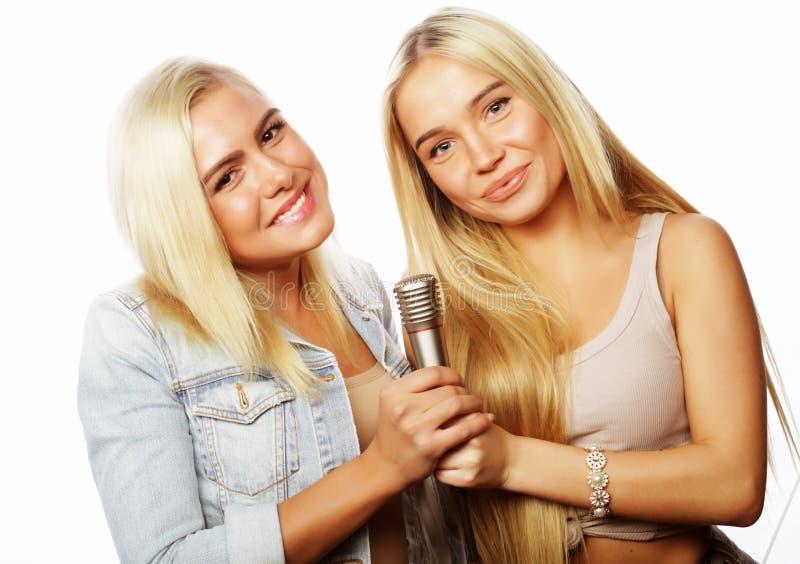 meninas do moderno da beleza com um microfone que cantam e que têm o divertimento fotografia de stock royalty free
