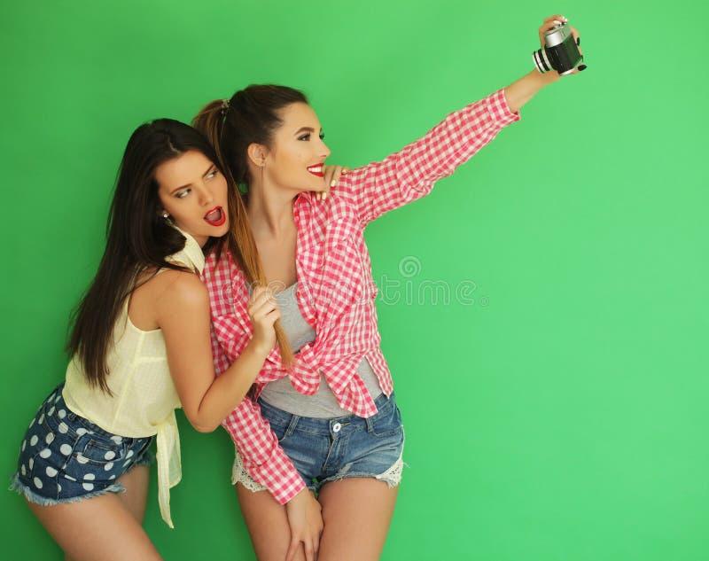 Meninas do moderno dos melhores amigos que estão junto com a câmera da foto fotografia de stock royalty free