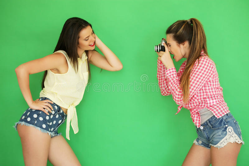 Meninas do moderno dos melhores amigos que estão junto com a câmera da foto imagem de stock royalty free
