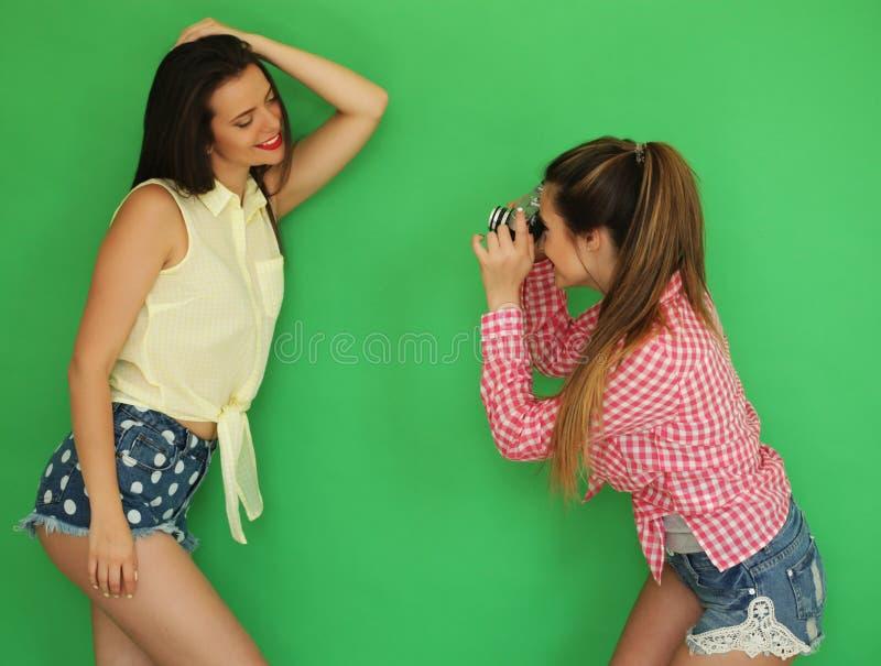 Meninas do moderno dos melhores amigos que estão junto com a câmera da foto fotografia de stock