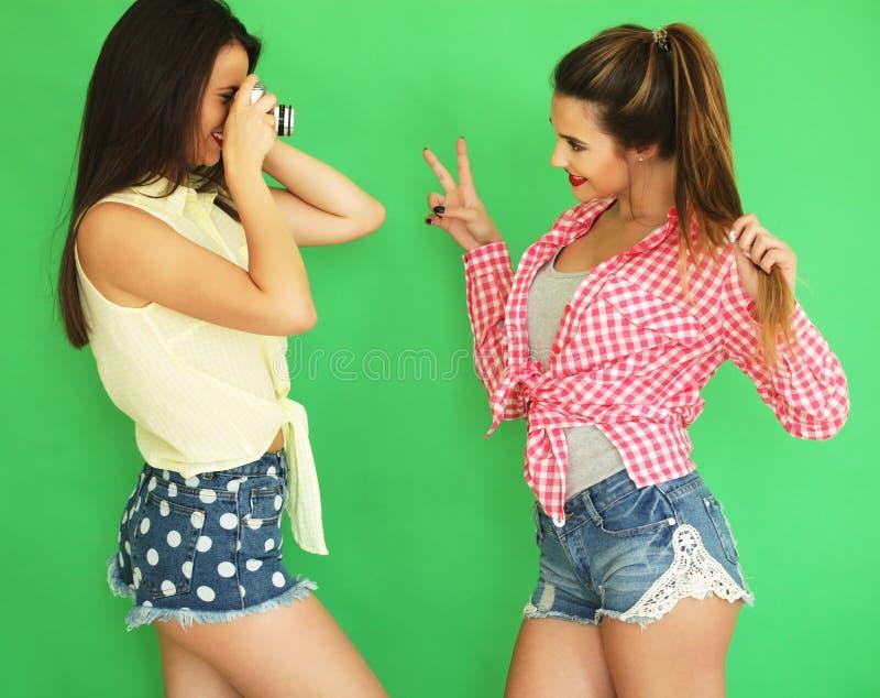 Meninas do moderno dos melhores amigos que estão junto com a câmera da foto imagens de stock royalty free
