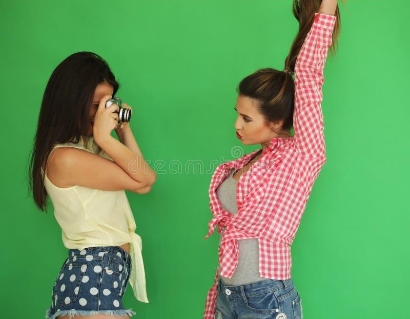 Meninas do moderno dos melhores amigos que estão junto com a câmera da foto imagem de stock
