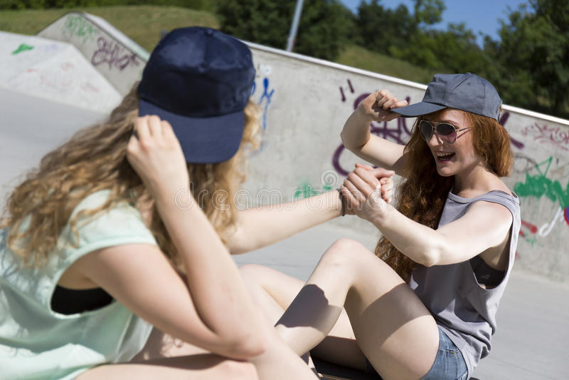 Meninas do moderno que sentam-se no parque do patim foto de stock
