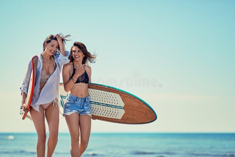 Meninas do surfista que guardam prancha felizes nas férias da praia ext fotografia de stock