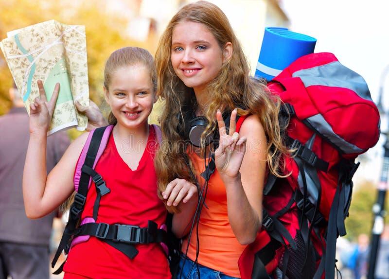 Meninas do viajante com a trouxa que procura o mapa do papel do turista da maneira foto de stock