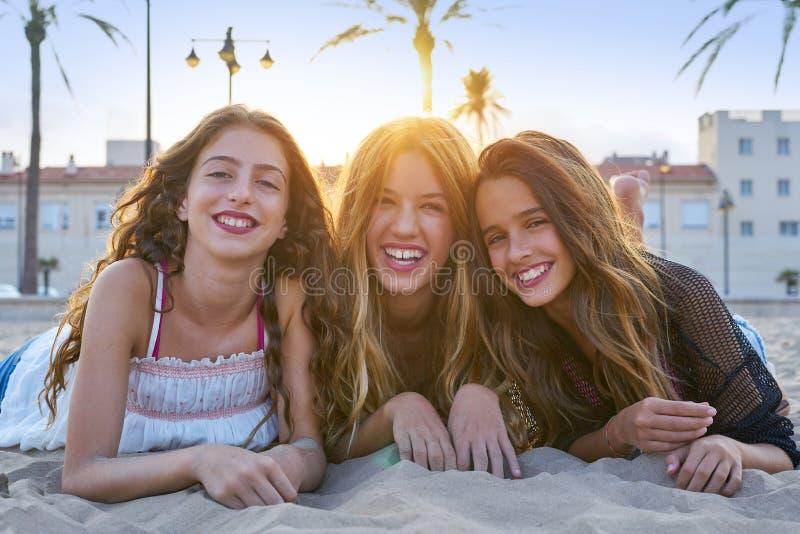 Meninas dos melhores amigos na areia da praia do por do sol fotografia de stock