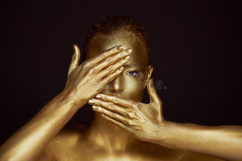 Meninas douradas impossíveis do retrato, mãos perto da cara Muito delicado e feminino Os olhos estão abertos Quadro das mãos imagem de stock royalty free