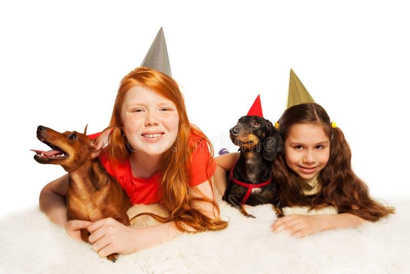 Meninas e animais de estimação que têm o divertimento na festa de anos fotos de stock