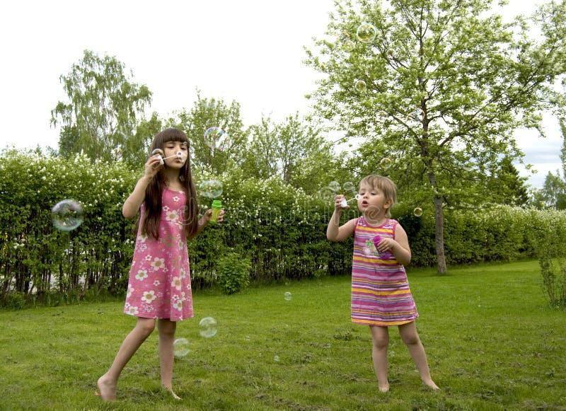 Meninas e bolhas de sabão imagens de stock