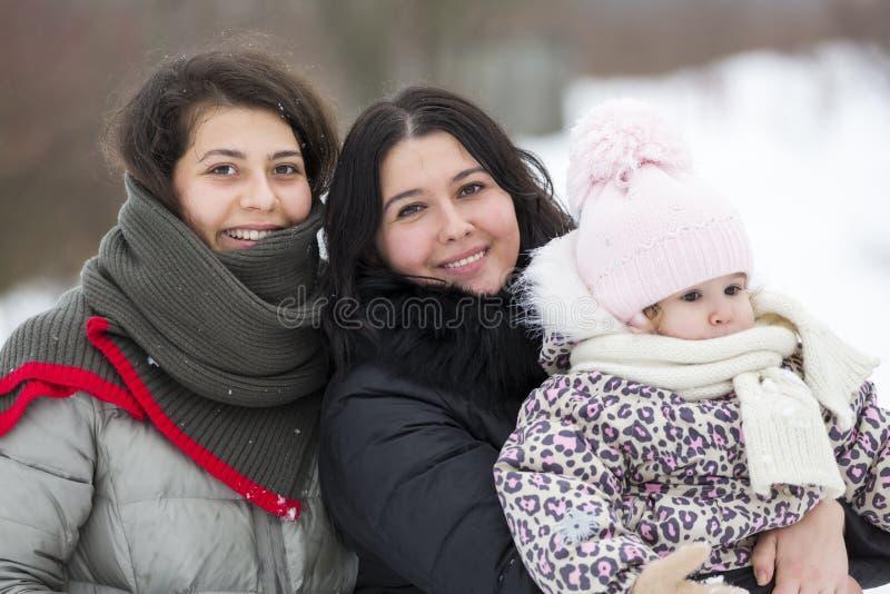 Meninas e criança felizes de sorriso no inverno Povos felizes fora foto de stock royalty free