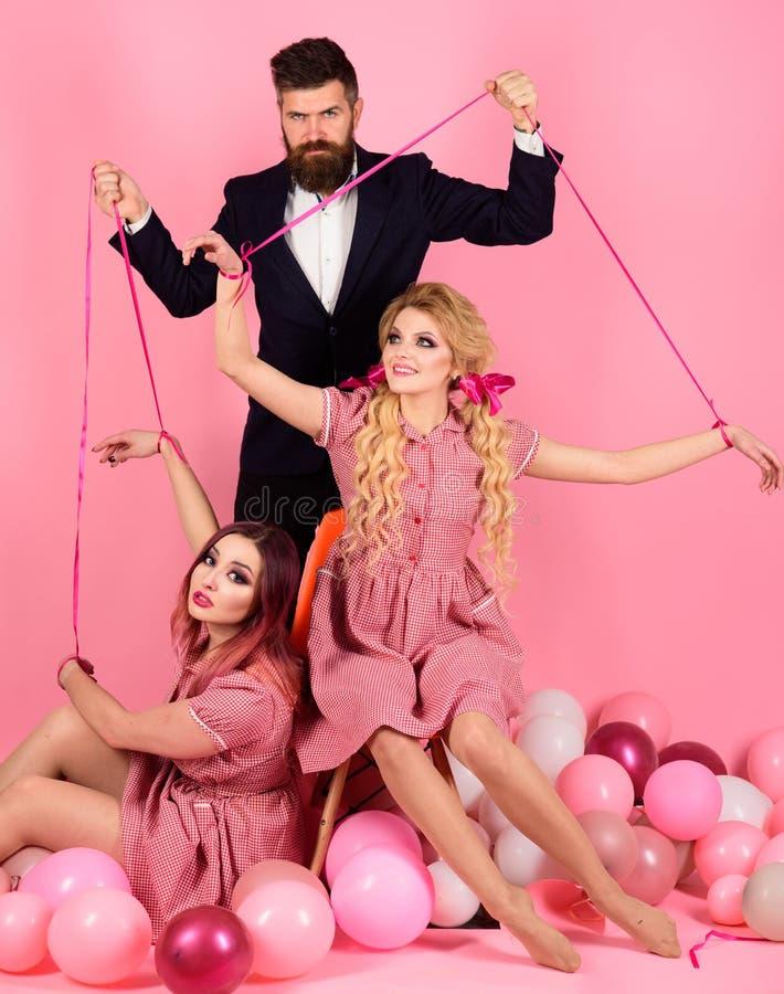 Meninas e homem loucos no rosa Halloween Idéia creativa Triângulo amoroso meninas retros e mestre em balões do partido vintage fotos de stock