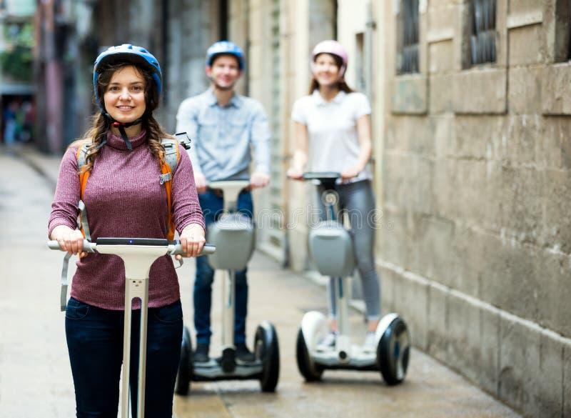 Meninas e indivíduo que viajam através da cidade por segways imagem de stock