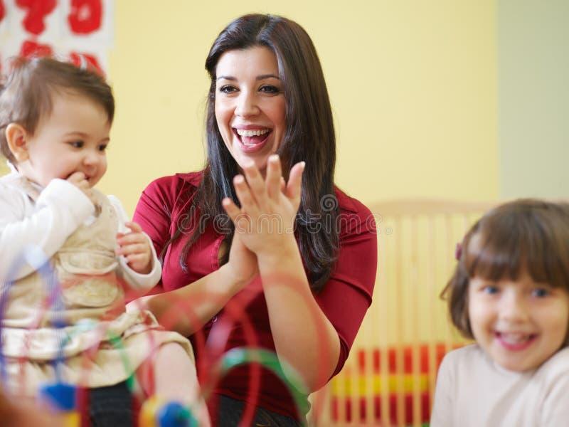 Meninas e professor fêmea no jardim de infância fotos de stock royalty free