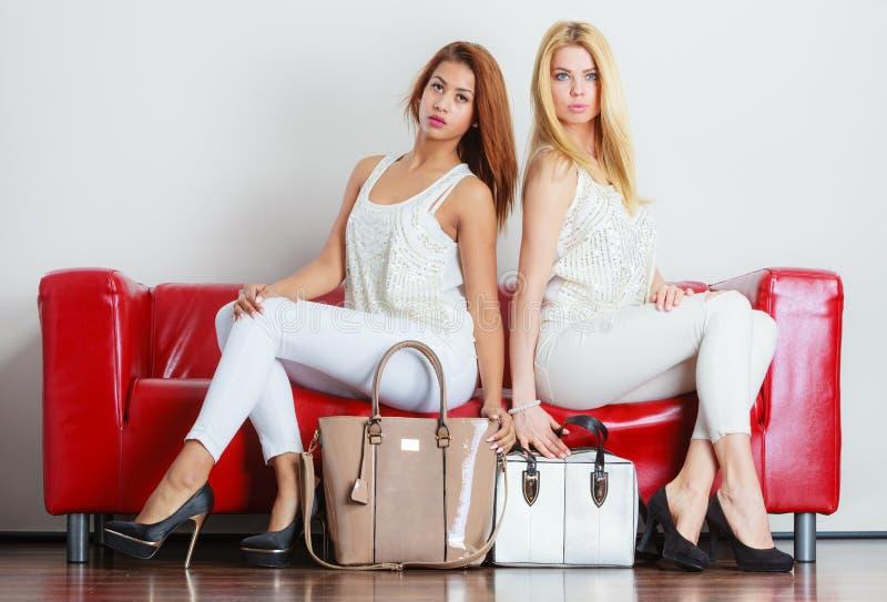 Meninas elegantes com as bolsas dos sacos no sofá vermelho imagens de stock royalty free