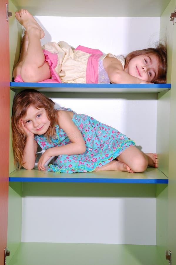 Meninas em prateleiras imagens de stock