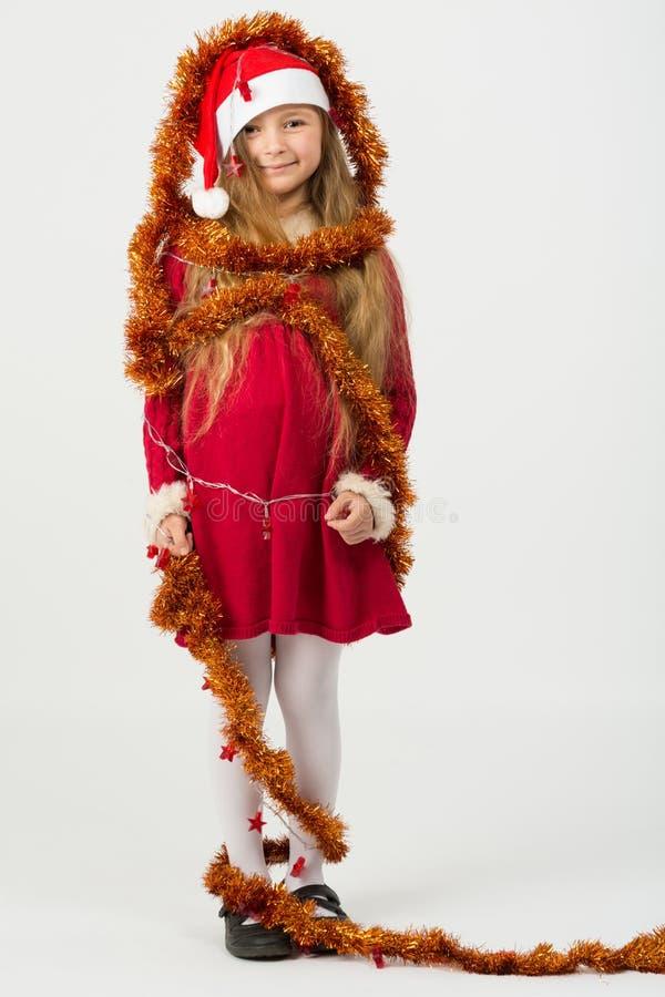 Meninas em um vestido vermelho nos tampões Santa Claus imagem de stock