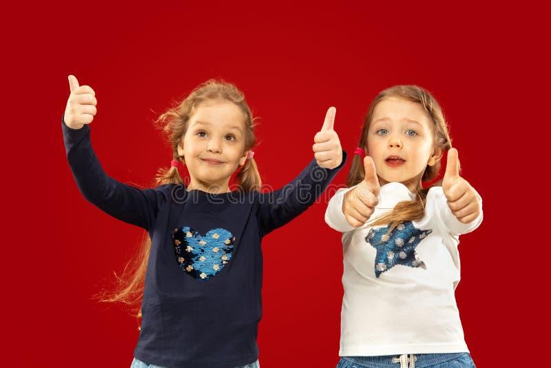 Meninas emocionais bonitas isoladas no fundo vermelho foto de stock royalty free