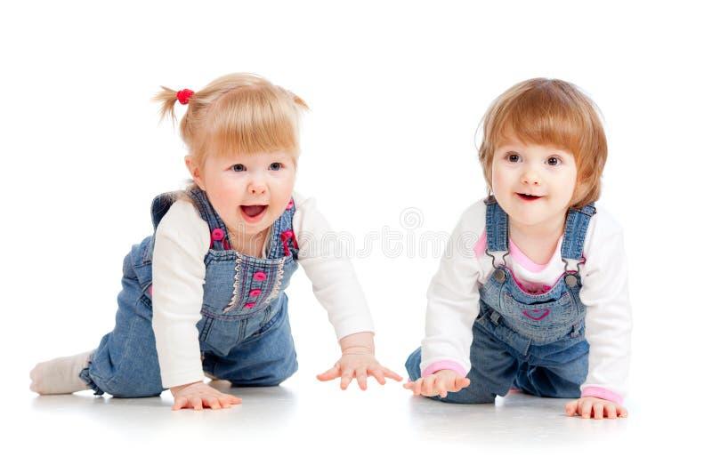 Meninas engraçadas dos miúdos que rastejam no assoalho fotografia de stock royalty free