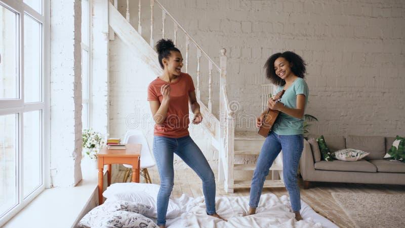 Meninas engraçadas novas da raça misturada que dançam o canto e o jogo da guitarra acústica em uma cama Irmãs que têm o lazer do  imagem de stock