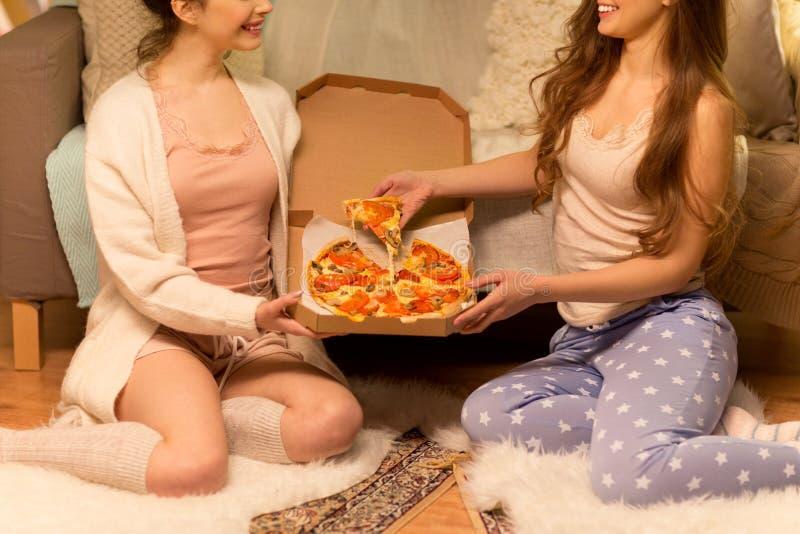 Meninas fêmeas ou adolescentes que comem a pizza afastada em casa fotografia de stock